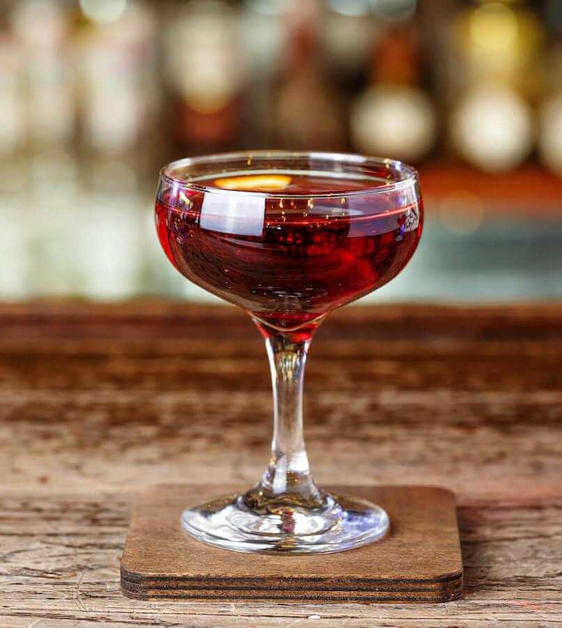 roter Manhattan Cocktail in einer Cocktailschale auf Holztisch