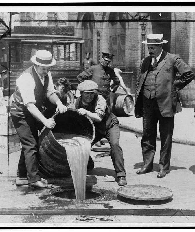2 Männer kippen während der Prohibition in Amerika ein Fass mit Whisky aus