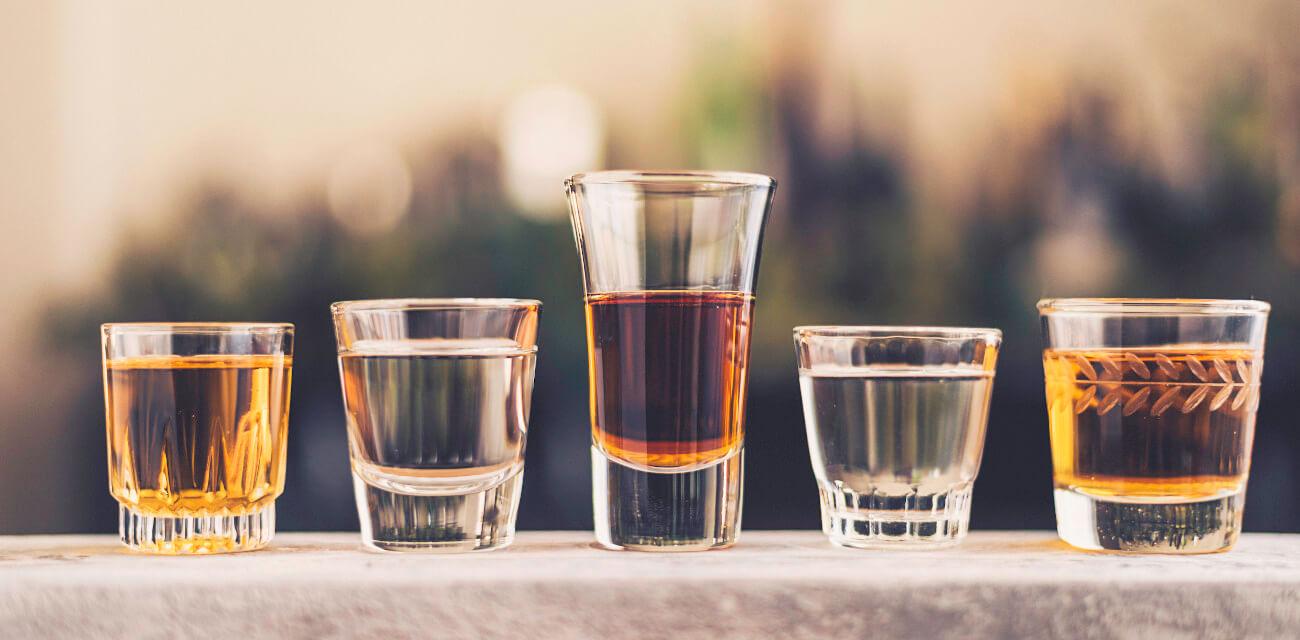 unterschiedliche kleine Gläser mit verschiedenen Spirituosen