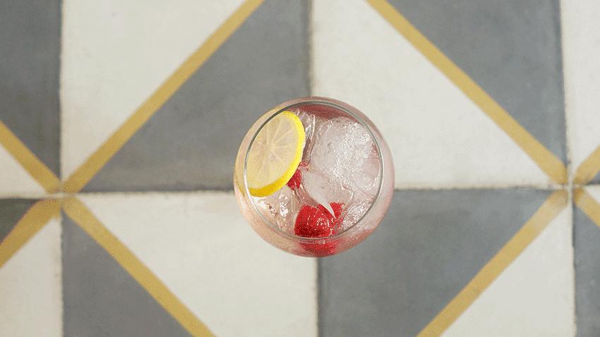 Glas mit Pox Tonic Cocktail von oben auf grau weißem Grund