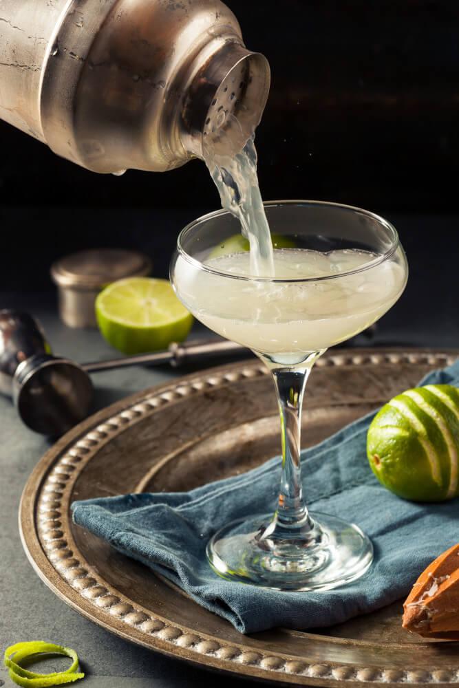 Gimlet Cocktail mit Rum wird us einem Shaker in eine Cocktailschale gegossen
