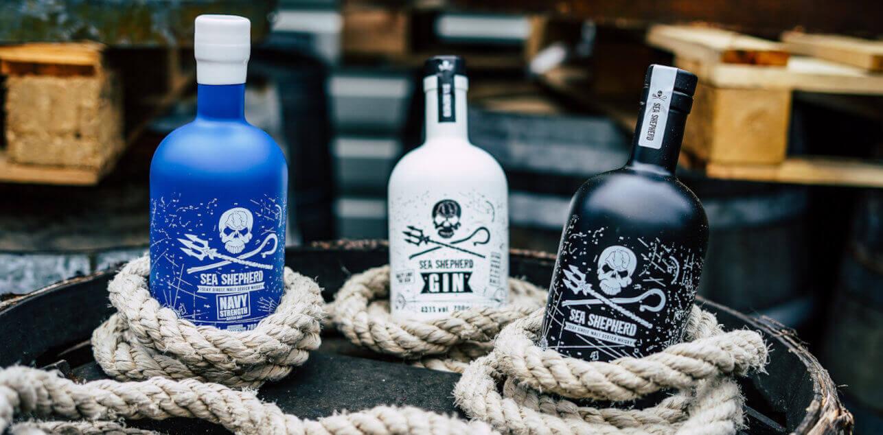 Eine schwarze, weißeund blaue Flasche zwischen weißem Tampen