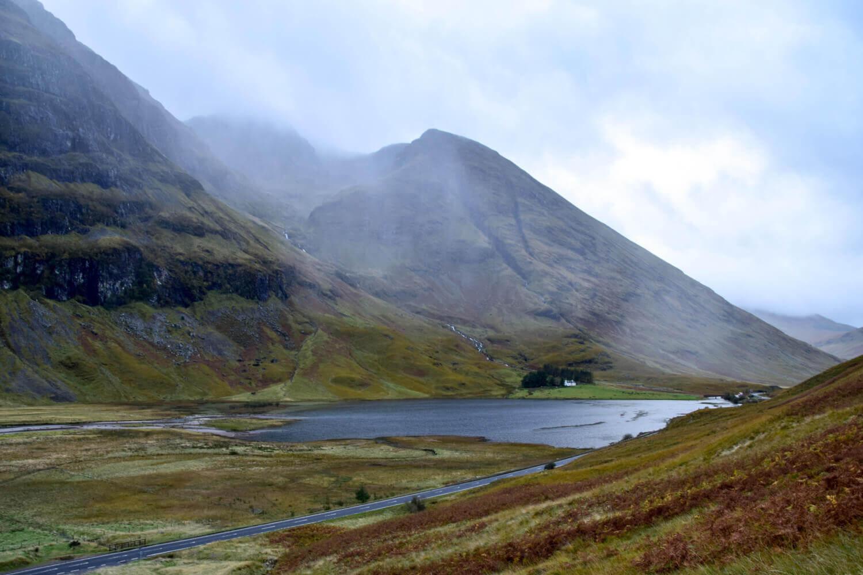Tal in den Highlands in Schottland mit See und Nebel