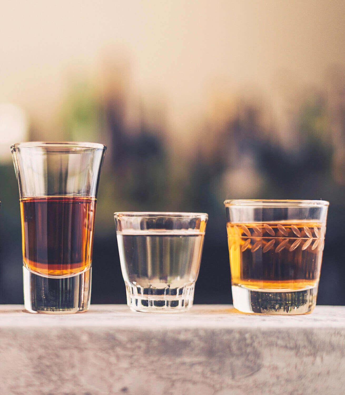 Drei verschiedene kleine Gläser mit unterschiedlichen Spirituosen