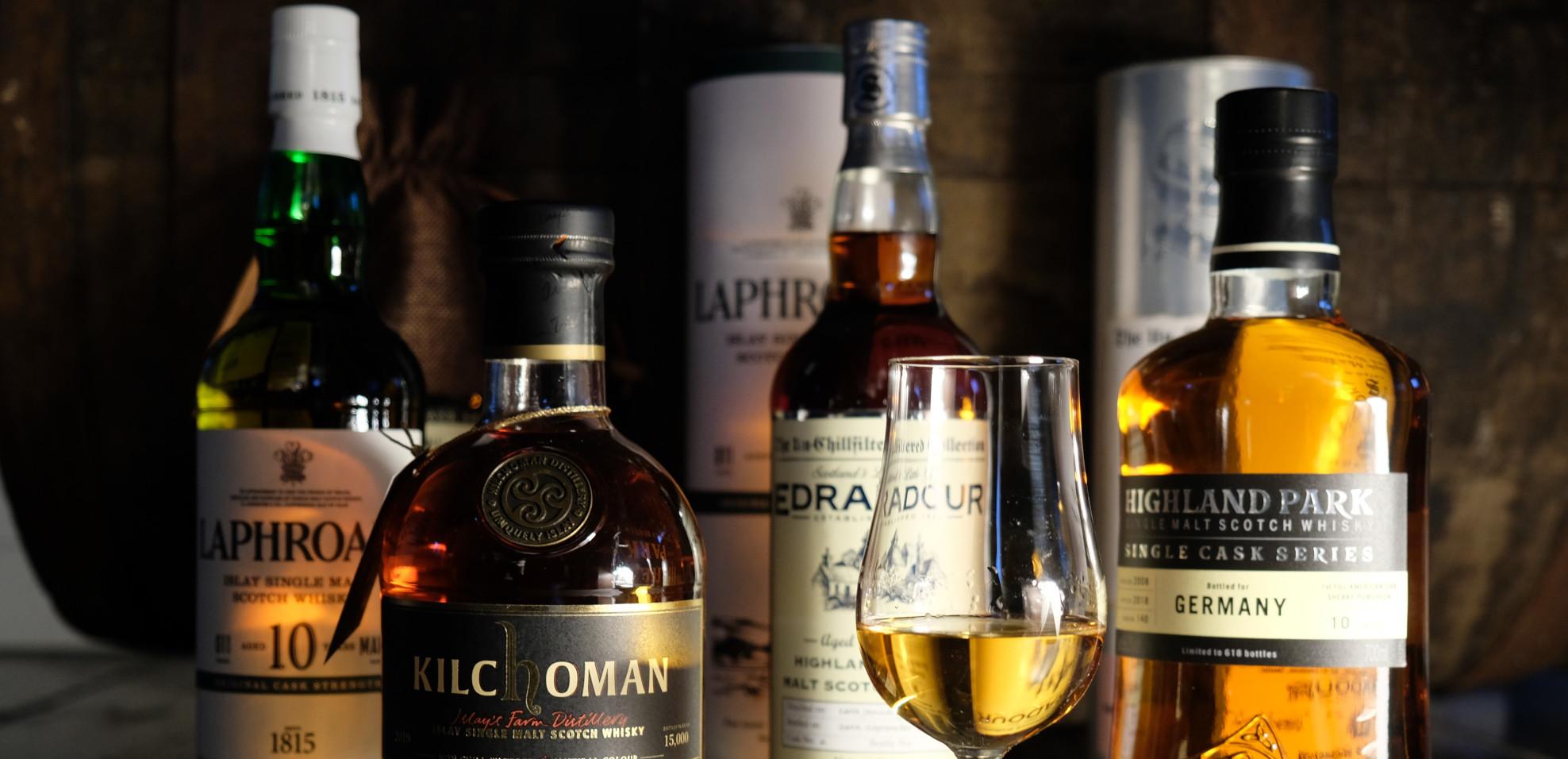 mehrere Flaschen Whisky vor einem Fass