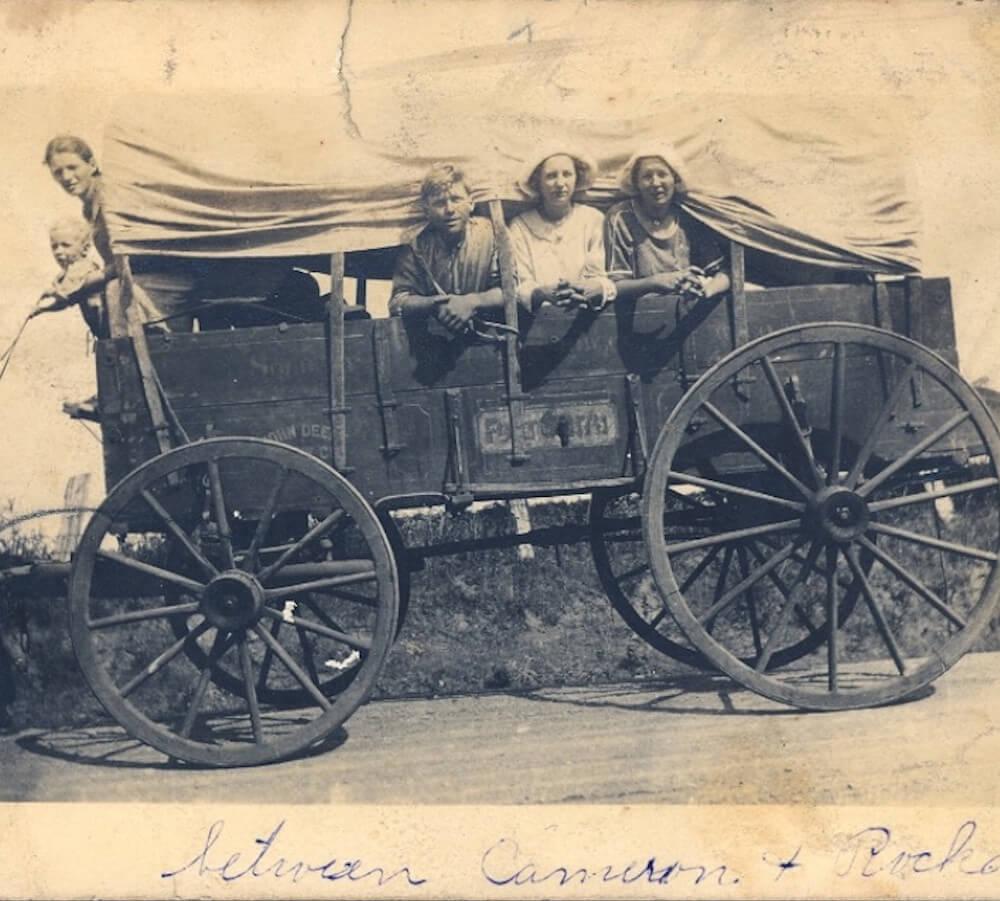 ein alter Planwagen aus den USA mit KIndern die seitlich herausschauen