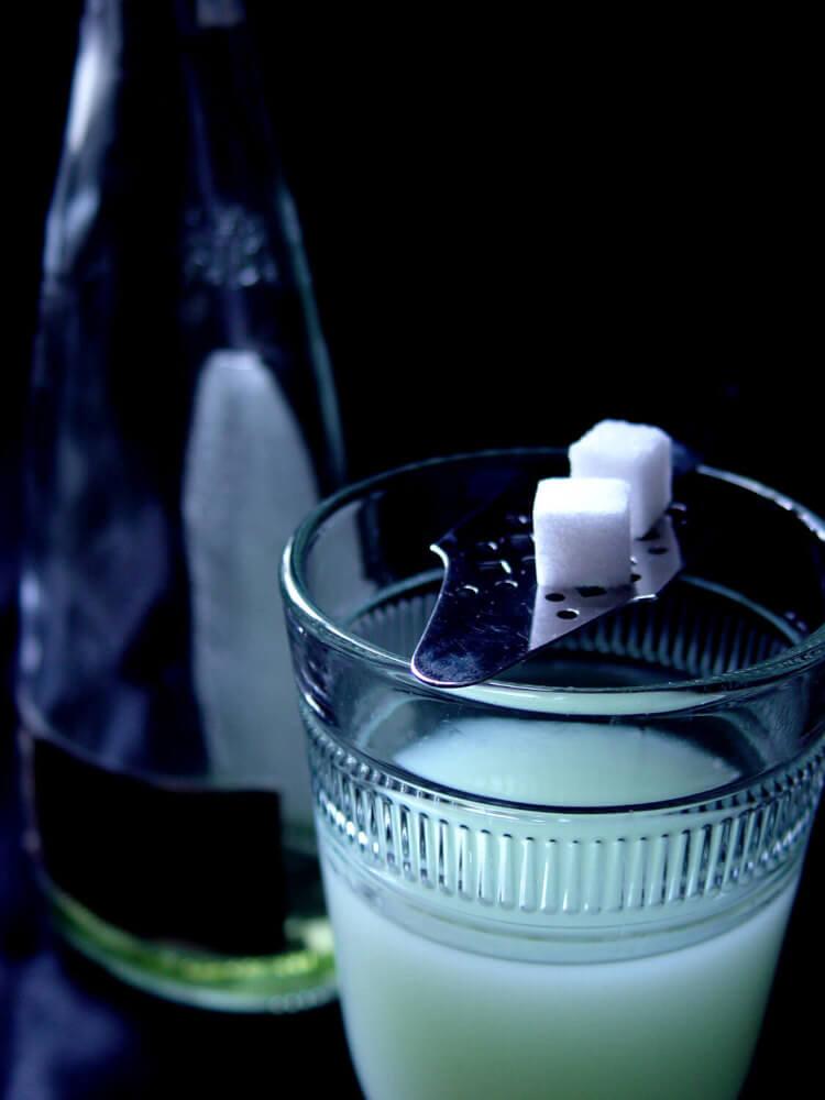 ein Glas mit Absinth und silbernem Loeffel mit zwei Zuckerwuerfel