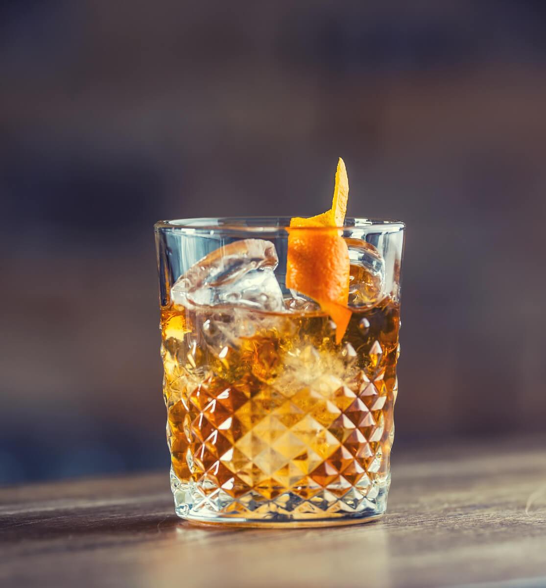 Old Fashioned Cocktail mit Rum in einem Tumbler mit Orangenschale
