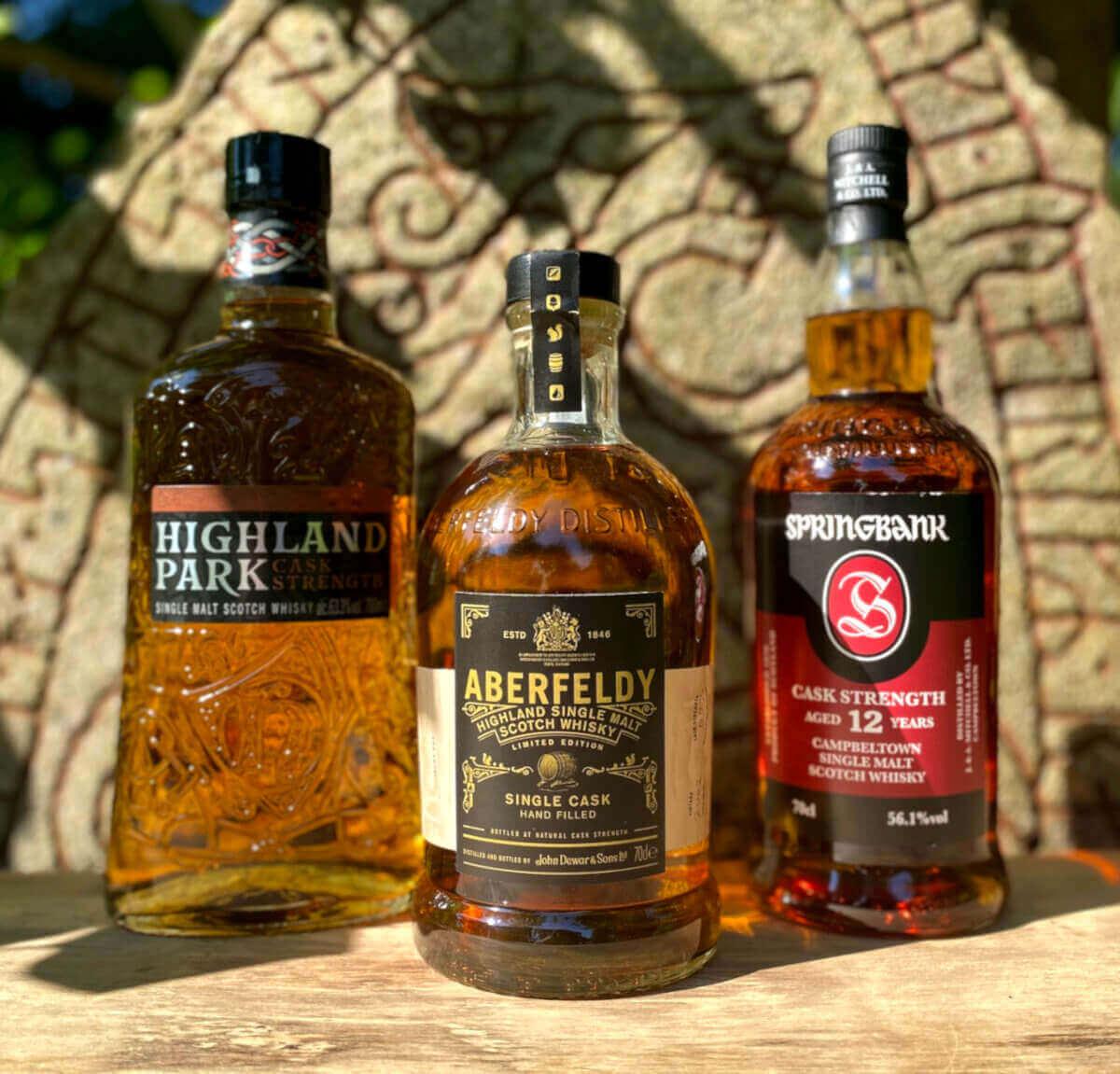 3 Flaschen Whisky vor Runen Stein mit roten Runen